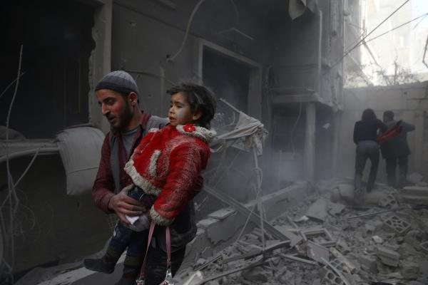 A man holds a child after an airstrike in the besieged town of Douma in eastern Ghouta in Damascus Syria